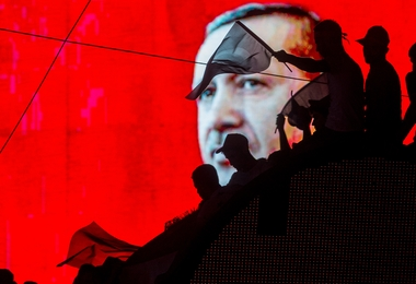 ANKARA, TURKEY - JULY 17:  People wave Turkish flags in front of an electronic billboard displaying the face of President Recep Tayyip Erdogan at a rally on the streets of Kizilay Square in reaction to the failed military coup on July 17, 2016 in Ankara, Turkey. Clean up operations are continuing in the aftermath of Friday's failed military coup attempt which claimed the lives of more than 250 people. In raids across Turkey 6,000 people have been arrested in relation to the failed coup including high-ranking soldiers and judges, Turkey's Justice Minister Bekir Bozdag has said.  (Photo by Chris McGrath/Getty Images)