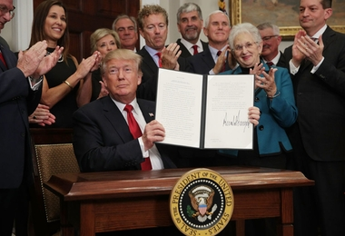 WASHINGTON, DC - OCTOBER 12:  U.S. President Donald Trump shows an executive order after he signed it as Sen. Rand Paul (R-KY), Vice President Mike Pence, Rep. Virginia Foxx (R-NC) and Secretary of Labor Alexander Acosta look on during an event in the Roosevelt Room of the White House October 12, 2017 in Washington, DC. President Trump signed the executive order to loosen restrictions on Affordable Care Act