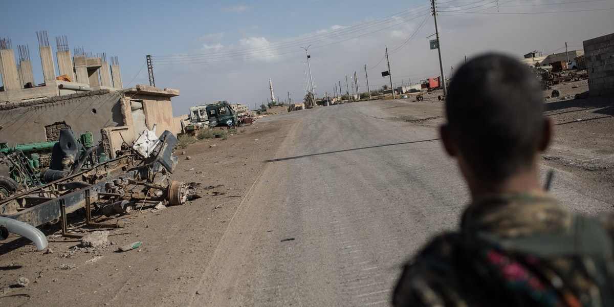 RAQQA, SYRIA - OCTOBER 30:  A fighter of the Syrian Democratic Forces (SDF) stands in an an empty street in the western neighborhood of Jazrah on the outskirts of Raqqa on October 30, 2017 in Raqqa, Syria. Following three and a half months of fighting Raqqa was liberated from the control of ISIL on October 19. Since then the city and surrounding neighborhood's have become a ghost town after being sealed off to civilians due to masses of landmines throughout the city.  (Photo by Chris McGrath/Getty Images)
