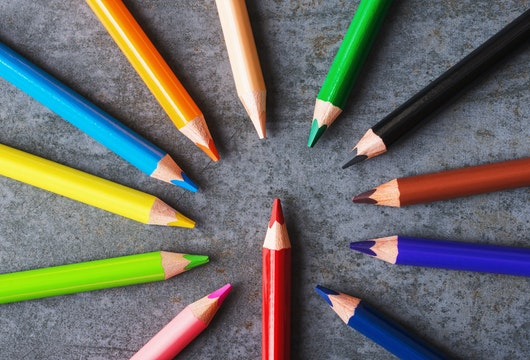 Multicolored pencils on grey background.