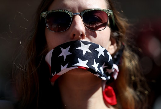 WASHINGTON, DC - MARCH 08:  A protester wears a patriotic bandana over her mouth during a march and rally to support women's health programs and protest the White House global gag rule on March 8, 2017 in Washington, DC. Hundreds of women marked International Women's Day with a march and rally outside of the White House to protest the White House global gag rule and support women's health programs.  (Photo by Justin Sullivan/Getty Images)