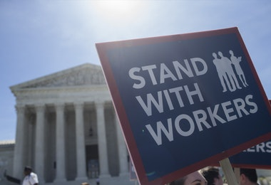 WASHINGTON, DC - JUNE 25: A demonstrator holds a sign in front of the U.S. Supreme Court on June 25, 2018 in Washington, DC. The high court is expected to issue decisions in six remaining cases, including the travel ban, public sector unions and redistricting, ahead of their end-of-June deadline this week.  (Photo by Zach Gibson/Getty Images)