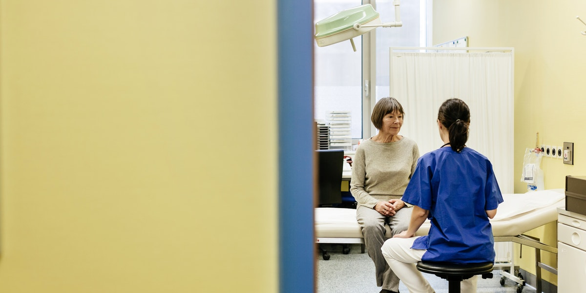 Mature female doctor talking to a female senior patient in doctors office