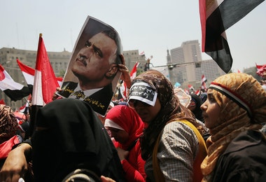 CAIRO, EGYPT - JULY 03:  Holding a picture of the second President of Egypt Gamal Abdel Nasser Hussein, hundreds of Egyptian protesters begin to gather in Tahrir Square as the deadline given by the military to Egyptian President Mohammed Morsi approaches on July 3, 2013 in Cairo, Egypt. The president gave a defiant speech last night and vowed to stay in power despite the military threats. As unrest spreads throughout the country, at least 23 people were killed in Cairo on Tuesday and over 200 others were injured.  (Photo by Spencer Platt/Getty Images)