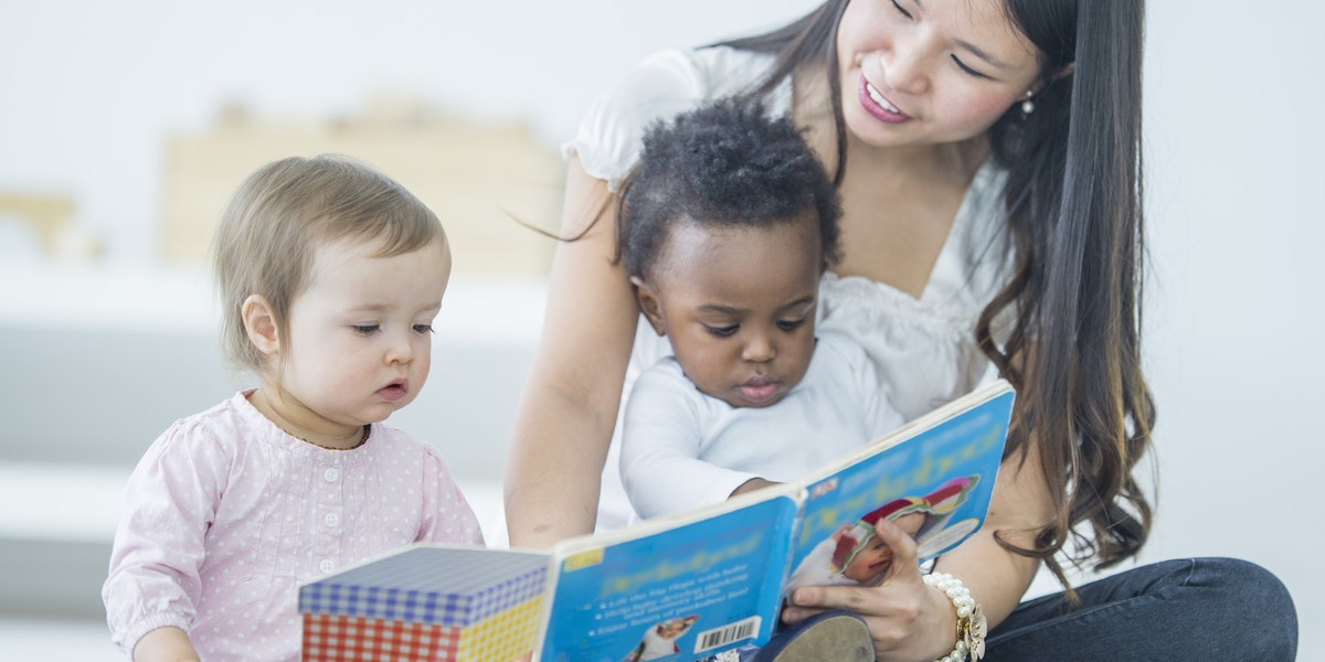Young Asian woman reading to two babies. The woman is sitting on the floor focusing on the book and reading while holding one child in her lap and one child sitting on the carpet next to the woman. Two children sitting with care taker, one baby of caucasian ethnicity and one baby of African Descent