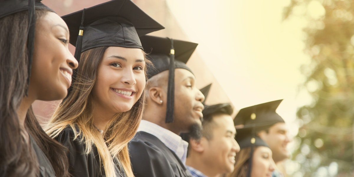 Latin descent girl waits in line during college graduation ceremony.   She looks at camera with a big smile as she wears a black cap and gown.
