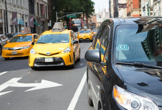 New York, USA - July 8, 2017: Uber car service in foreground picking up passenger on Broadway in Lower Manhattan shopping district.  Customer call on an Uber car by using an app on the mobile phone
