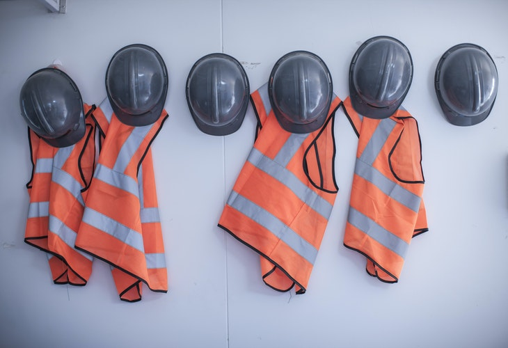 safety vests and hard hats hanging on wall in site office