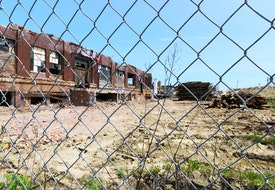 Chicago, USA - May 21, 2016: Derelict Chicago industrial building, half demolished,  viewed through a chainlink fence. McKinley Park community area, Southwest Side. No people.