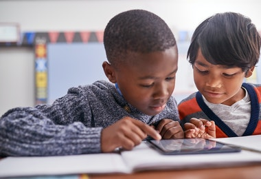 Cropped shot of elementary school children using a tablet in class