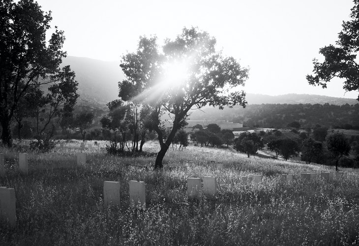 IRAQ. Barzan. July 14, 2014. The sun rises over a memorial cemetery in the village of Barzan, the hometown of Kurdish leader Masoud Barzani, where the remains of 603 Kurdish villagers, killed by Saddam Hussein forces during the late 1980's Al Anfal campaign against the Kurds, have been laid to rest.Many of the victims were sent to southern Iraq, where they were executed or buried alive in mass graves. The remains of 603 Kurdish villagers from Barzan found in mass graves in southern Iraq have been returned and laid to rest in this memorial cemetery on a hill outside the village.