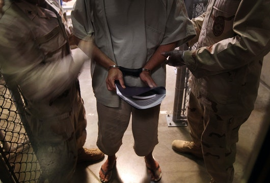 GUANTANAMO BAY, CUBA - MARCH 30:  (EDITORS NOTE: Image has been reviewed by the U.S. Military prior to transmission.) U.S. Navy guards escort a detainee after a