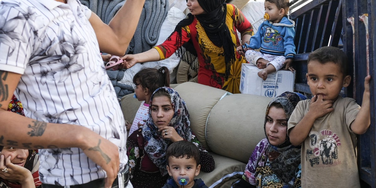 DOHUK, IRAQ - OCTOBER 24: A family from Qamishli, Syria arrives at Badarash IDPs camp which has continued to swell for Syrian Kurdish refugees fleeing the recent Turkish incursion in Rojava. on October 24, 2019 in Dohuk, Iraq. In seven days UNHCR reports that 7,100 have now arrived to the camp.  Many fleeing have said saying they paid to be smuggled through the Syrian border.  (Photo by Byron Smith/Getty Images)