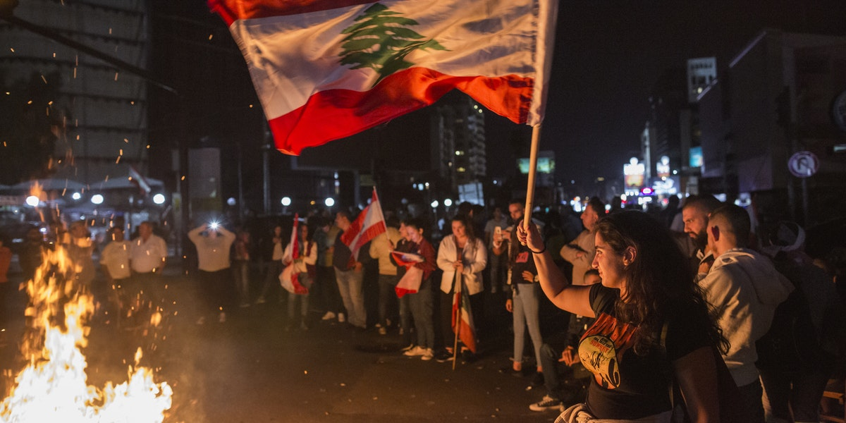 BEIRUT, LEBANON - NOVEMBER 03: A protester waves a Lebanese flag as anti-government demonstrators block the Chevrolet intersection on November 3, 2019 in Beirut, Lebanon. The country has seen 18 days of unrest after demonstrators took to the streets to protest tax hikes and government corruption. (Photo by Sam Tarling/Getty Images) (Photo by Getty Images/Getty Images)