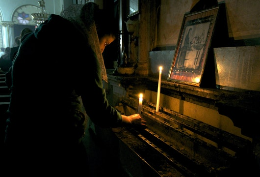 A worshipper lights a candle at the Syriac Orthodox Church in Al-Darbasiyah, Hasakah province November 13, 2013. Due to the clashes in north-eastern Syria, many Christians have fled the area seeking safety elsewhere, activists say. Picture taken November 13, 2013.  REUTERS/Stringer (SYRIA - Tags: CONFLICT RELIGION CIVIL UNREST) - GM1E9BF1K1001