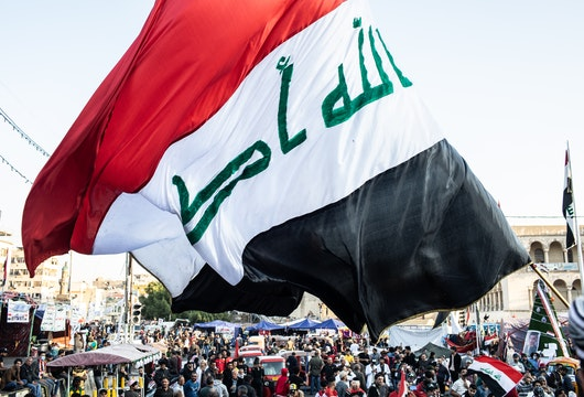 BAGHDAD, IRAQ - NOVEMBER 21: A flag waves over Tahrir Square on November 21, 2019 in Baghdad, Iraq. Thousands of demonstrators have occupied Baghdad's center Tahrir Square since October 1, calling for government and policy reform. For many, Tahrir Square, which protesters are calling