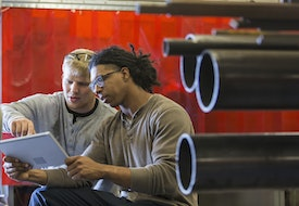 Two young multi-ethnic men using a digital tablet.  They are in a factory or workshop. The mixed race man is holding the tablet, and the other man is pointing to the screen.
