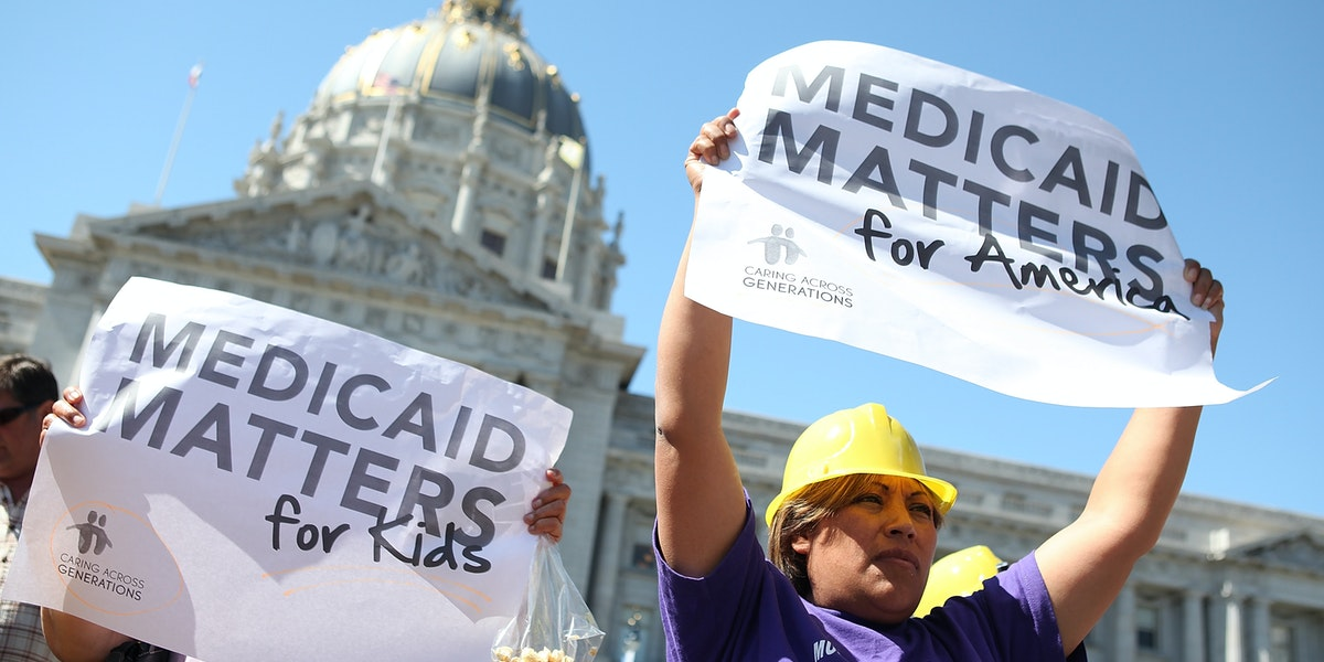 SAN FRANCISCO, CA - SEPTEMBER 21:  Protestors carry signs as they demonstrate against proposed cuts to Medical and Medicare outside San Francisco city hall on September 21, 2011 in San Francisco, California.  Dozens of disabled people staged a protest against proposed cuts to Medical, Medicare and Medicaid programs.  (Photo by Justin Sullivan/Getty Images)