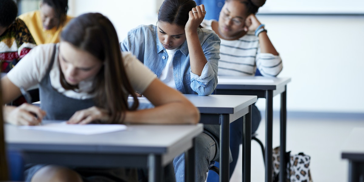 Young multi-ethnic female university students writing on papers at desks during exams in community college classroom