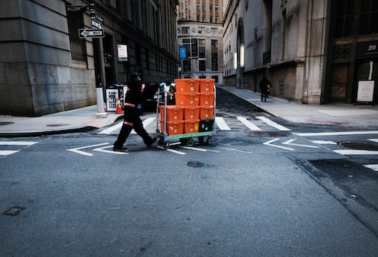 NEW YORK CITY,  - MARCH 24:  A man makes deliveries near Wall Street as people stay away from the area due to the coronavirus on March 24, 2020 in New York City. Across the country schools, businesses and places of work have either been shut down or are restricting hours of operation as health officials try to slow the spread of COVID-19.  (Photo by Spencer Platt/Getty Images)