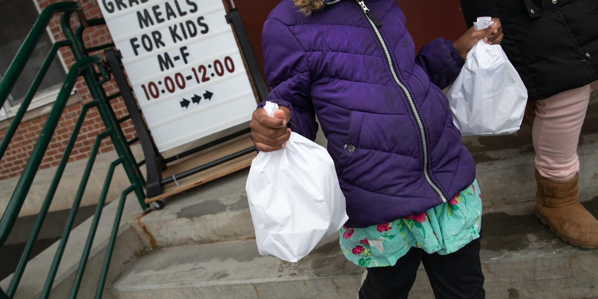 STAMFORD,  - MARCH 17: A student carries home bagged meals given out as part of Stamford Public Schools'