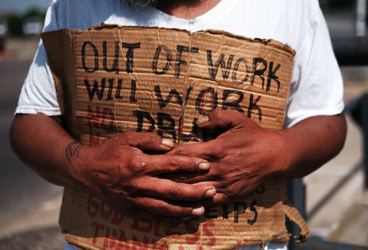 LAWRENCE, MASSACHUSETTS - AUGUST 16: George, who is homeless, panhandles along a street in Lawrence on August 16, 2019 in Lawrence, Massachusetts. Lawrence, once one of America's great manufacturing cities with immigrants from around the world coming to work in its textile and wool processing mills, has struggled to find its economic base since the decline of manufacturing. Despite a strong national economy, Lawrence, and many mid-size American cities and towns, are struggling with persistent joblessness, an opioid epidemic and a lack of affordable housing. While Lawrence is witnessing pockets of investment, many of its residents are facing economic hardship. Currently one-third of Lawrence's children live in poverty, 36 percent of residents receive aid under the Supplemental Nutrition Assistance Program and just over 24 percent of residents live in poverty. (Photo by Spencer Platt/Getty Images)