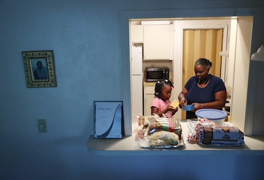 MIAMI, FLORIDA - MARCH 26: Willie Mae Daniels makes melted cheese sandwiches with her granddaughter, Karyah Davis,6, after being laid off from her job as a food service cashier at the University of Miami on March 17 as the university joins in the effort to fight the coronavirus on March 26, 2020 in Miami, Florida. Mrs. Daniels said that she has applied for unemployment benefits as she joins roughly 3.3 million Americans nationwide who are looking for unemployment benefits as restaurants, hotels, universities, stores and more shut down in an effort to slow the spread of COVID-19. (Photo by Joe Raedle/Getty Images)