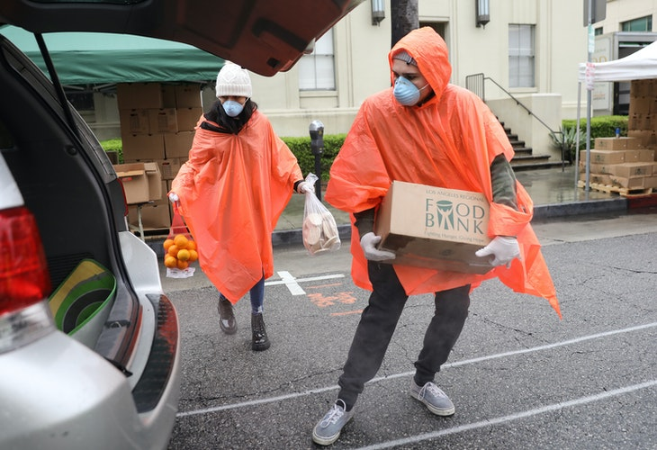 VAN NUYS, CALIFORNIA - APRIL 09: Volunteers load food into a recipient's trunk at a Food Bank distribution for those in need as the coronavirus pandemic continues on April 9, 2020 in Van Nuys, California. Organizers said they had distributed food for 1,500 families amid the spread of COVID-19.  (Photo by Mario Tama/Getty Images)
