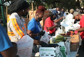OPA LOCKA, FLORIDA - APRIL 14: City of Opa-locka employees and volunteers prepare bags of food, provided by the food bank Feeding South Florida, to be given out to the needy at a drive-thru distribution site on April 14, 2020 in Opa-locka, Florida. Feeding South Florida has seen a 600 percent increase in those asking for food aid as people, some of whom have lost jobs, need to make ends meet during the coronavirus pandemic.  (Photo by Joe Raedle/Getty Images)