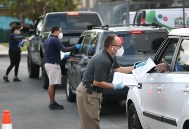 HIALEAH, FLORIDA - APRIL 08: Eddie Rodriguez (R) and other City of Hialeah employees hand out unemployment applications to people in their vehicles in front of the John F. Kennedy Library on April 08, 2020 in Hialeah, Florida. The city is distributing the printed unemployment forms to residents as people continue to have issues with access to the state of Florida's unemployment website in the midst of widespread layoffs due to businesses closing during the coronavirus pandemic. (Photo by Joe Raedle/Getty Images)