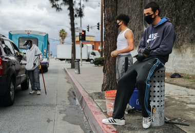 LOS ANGELES, CALIFORNIA  - APRIL 06: Young men wear face masks while waiting to clean windshields for extra cash amid the coronavirus pandemic on April 6, 2020 in south Los Angeles, California. More than 10,000 people have now died in the U.S. from COVID-19. (Photo by Mario Tama/Getty Images)