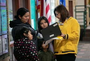 STAMFORD,  - MARCH 17: Bilingual teacher Maria Sanislo (R) explains a Google Chromebook to a family at KT Murphy Elementary School on March 17, 2020 in Stamford, Connecticut. Stamford Public Schools closed last week to help slow the spread of COVID-19, and students are now