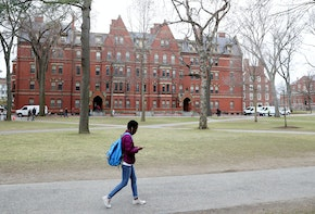 CAMBRIDGE, MASSACHUSETTS - MARCH 12: A student walks through Harvard Yard on the campus of Harvard University on March 12, 2020 in Cambridge, Massachusetts. Students have been asked to move out of their dorms by March 15 due to the Coronavirus (COVID-19) risk. All classes will be moved online for the rest of the spring semester.  (Photo by Maddie Meyer/Getty Images)