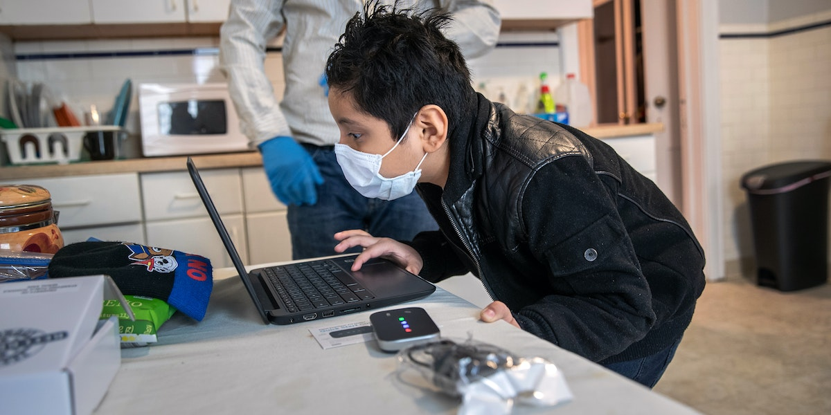 STAMFORD, CONNECTICUT - APRIL 18: (EDITORIAL USE ONLY) Recovering from COVID-19, Guatemalan immigrant Junior, 7, tries to log-in to his school ChromeBook on April 18, 2020 in Stamford, Connecticut. He and his father Marvin have been sick and in quarantine at home for several weeks. His mother, Zully, a Guatemalan asylum seeker also sick with COVID-19, gave birth to baby boy named Neysel by emergency C-section at Stamford Hospital. Junior's Bilingual /ESL teacher Luciana Lira at Hart Magnet Elementary in Stamford, became temporary guardian for the newborn, while the family recovers. Lira continues remote teaching her elementary school students, while also caring for the infant at home. She plans to continue doing so until the Guatemalan family all test negative for the virus and can care for the child themselves. (Photo by John Moore/Getty Images)