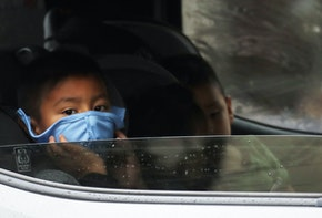 VAN NUYS, CALIFORNIA - APRIL 09: A boy wears a face mask as food is delivered to his truck at a Food Bank distribution for those in need as the coronavirus pandemic continues on April 9, 2020 in Van Nuys, California. Organizers said they had distributed food for 1,500 families amid the spread of COVID-19.  (Photo by Mario Tama/Getty Images)