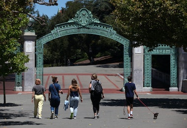 BERKELEY, CALIFORNIA - JULY 22: People walk towards Sather Gate on the U.C. Berkeley campus on July 22, 2020 in Berkeley, California. U.C. Berkeley announced plans on Tuesday to move to online education for the start of the school's fall semester due to the coronavirus COVID-19 pandemic. (Photo by Justin Sullivan/Getty Images)