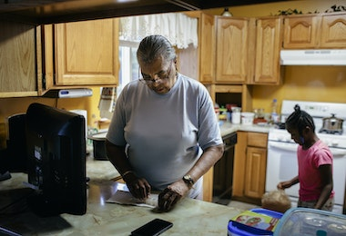 Senior woman in home kitchen sorting weekly medication. Her granddaughter is standing in the background. Member of a