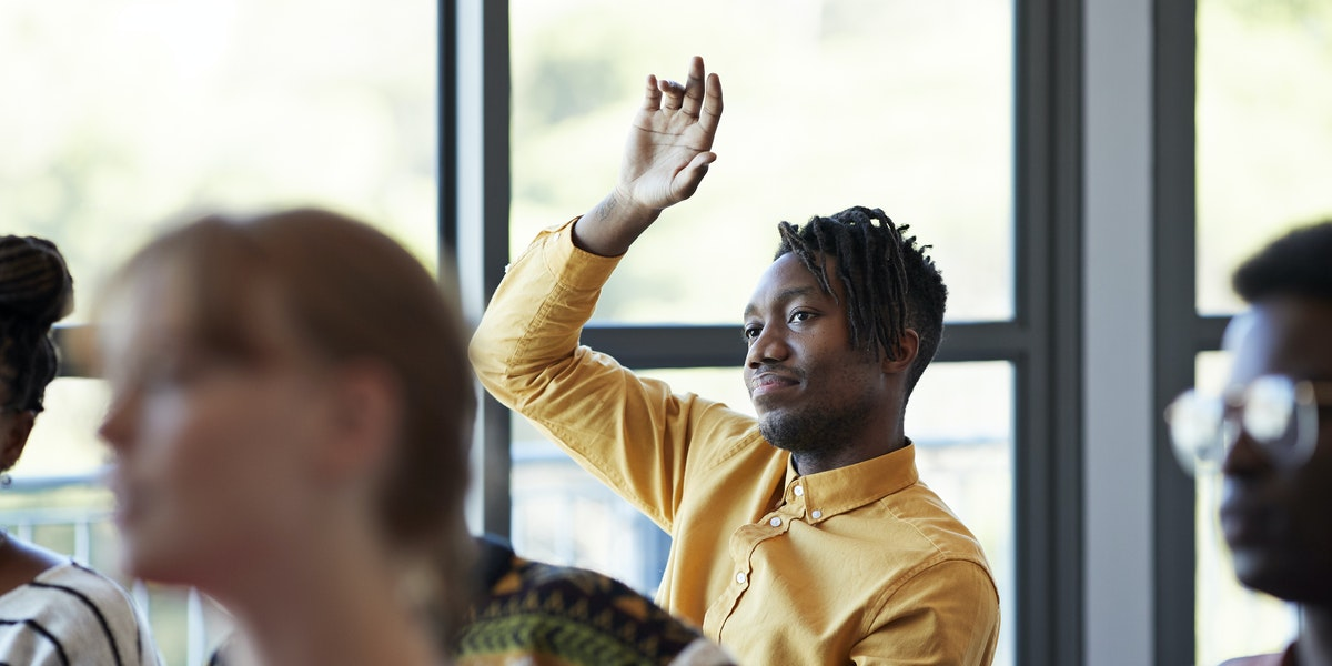 Confident young male student looking away while sitting with arm raised amidst friends in classroom against window at community college