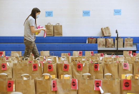 PROVO, UT - MAY 18:  A teacher puts final items into paper bags with the personal belongings of students at Freedom Preparatory Academy waiting for parents to come and pick them up on May 18, 2020 in Provo, Utah. Freedom Academy an elementary school was closed on March 16, 2020 along with all other school in Utah due to the order of the Utah Governor due to the COVID-19 pandemic. (Photo by George Frey/Getty Images)