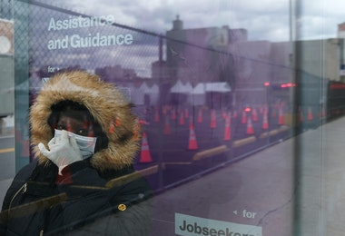 NEW YORK, NY - APRIL 10: A woman waits for a bus near a coronavirus testing site in Brooklyn on April 10, 2020 in the Brooklyn borough of New York City. According to John Hopkins University, the global death toll from COVID-19 has now reached 100,000 worldwide with many experts believing that the number is actually higher.   (Photo by Spencer Platt/Getty Images)