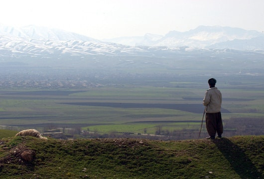 HALABJA, IRAQ - FEBRUARY 24:  A shepherd stands looking out towards the mountains where a mass grave site of most of the victims of the March 16, 1988 chemical attacks on Halabja are buried February 24, 2004 in Halabja, Iraq. In Halabja, approximately 5,000 innocent civilians, mostly women and children (75 percent), immediately perished due to chemical attacks committed allegedly by the Iraqi regime. The chemical attacks were said to have involved mustard gas, nerve agents and possibly cyanide. The attack on Halabja took place amidst the infamous al-Anfal campaign, in which former Iraqi Dictator Saddam Hussein is alleged to have brutally repressed yet another of the Kurdish revolts during the Iran-Iraq war at the time.  (Photo by Marco Di Lauro/Getty Images)