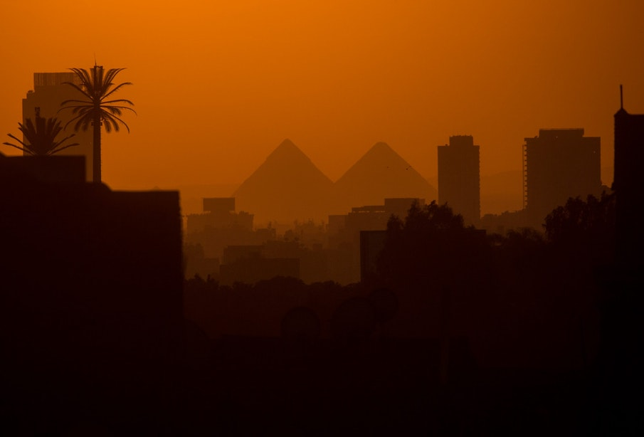 CAIRO, EGYPT - DECEMBER 15: City buildings are seen in front of the famous Giza Pyramids on December 15, 2016 in Cairo, Egypt. Since the 2011 Arab Spring, Egyptians have been facing a crisis, the uprising brought numerous political changes, but also economic turmoil, increased terror attacks and the unravelling of the once strong tourism sector. In recent weeks Egypt has again been hit by multiple bomb blasts, the most recent killed 26 Christians inside the St Peter and St Paul Church during Sunday mass. As Christians took to the streets chanting anti-government slogans, fears grow of an escalation in militant activity which would further deal damage to a country trying to rebuild. In recent months protests against rising fuel and food prices, calls for mass anti-government demonstrations and the continued terror attacks have seen Egyptian president Abdel Fattah Al-Sisi, suffer a significant drop in popularity. Mr. Al-Sisi has promised change, fearing anger and desperation could lead to popular unrest, however inflation currently sits at the highest level in seven years, jobless rates are above 13percent and more than 90million people are said to be living in poverty. The outlook forced the government to seek a $12 billion bailout from the International Monetary Fund, pushing the country to float the Egyptian pound to qualify for the loan. The move led to a sharp devaluation of the Egyptian pound which now sits at 18EGP to the dollar. The turmoil is affecting not only the poor but both the middle-class and the wealthy as food and commodity prices skyrocket.  (Photo by Chris McGrath/Getty Images)