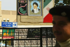 AL-MUNTHRIYA, IRAQ - MARCH 15:  An Iraqi border guard stands in front of a picture of the late Iranian leader Ayatollah Khomeini, which is displayed on the Iranian side March 15, 2004 at the Al-Munthriya border crossing in Al-Munthriya, Iraq.  The US has begun tightening security over Iraq's 1,300km border with Iran over the weekend, as six more US servicemen were killed in attacks by forces opposed to the 11-month old occupation. Currently there are 19 legal crossing points between Iraq and Iran, but this will be reduced to three and each traveler will have to produce a passport and be registered, Paul Bremer, the senior US administrator in Iraq, announced Saturday. The number of Iraqi border guards are to be doubled to 16,000.  (Photo by Spencer Platt/Getty Images)