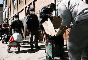 NEW YORK, NEW YORK - OCTOBER 17: People receive food at the Thessalonica Christian Church during a distribution on October 17, 2020 in New York City. The Bronx, a borough which has long struggled with poverty and neglect, has been especially impacted by the COVID-19 pandemic. The official unemployment rate in the Bronx is 21% while the unofficial number is presumed to be almost twice that. With many residents unable to afford health care and being home to a significant amount of front-line workers, the Bronx has the highest COVID-19 death rate in New York City.  (Photo by Spencer Platt/Getty Images)