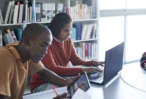 Young woman using laptop while sitting by friend studying at desk against bookshelf in library