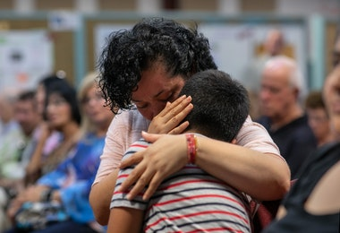 STAMFORD, CONNECTICUT - AUGUST 12: A Mexican immigrant embraces her son at town hall-style event held to reassure the nervous local immigrant community on August 12, 2019 in Stamford, Connecticut. State and local government leaders listened as immigrants spoke of their fears in an atmosphere of racially-charged tweets from President Trump and following the El Paso mass shooting, which targeted people of Mexican heritage. Officials reassured them they would continue to receive support in the state Connecticut, even as the federal government pursues the President's anti-immigrant agenda. The event was held at the Building One Community immigrant center in Stamford.  (Photo by John Moore/Getty Images)