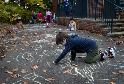 STAMFORD, CONNECTICUT - OCTOBER 21: A first grader draws during recess at Stark Elementary School on October 21, 2020 in Stamford, Connecticut. Stamford Public Schools is continuing the fall semester with a hybrid model of in-class and distance learning, occasionally quarantining individual classes when a student or faculty member tests positive for COVID-19.  (Photo by John Moore/Getty Images)