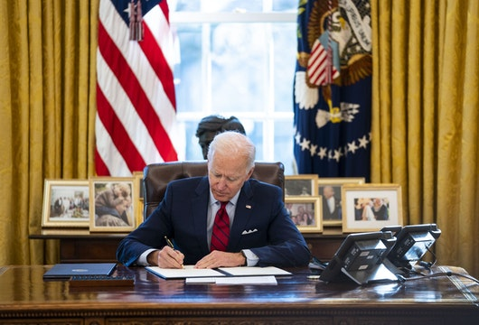 WASHINGTON, DC - JANUARY 28: U.S. President Joe Biden signs executive actions in the Oval Office of the White House on January 28, 2021 in Washington, DC. President Biden signed a series of executive actions Thursday afternoon aimed at expanding access to health care, including re-opening enrollment for health care offered through the federal marketplace created under the Affordable Care Act. (Photo by Doug Mills-Pool/Getty Images)
