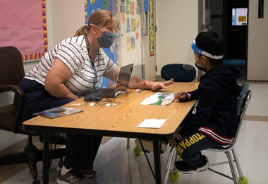 STAMFORD, CONNECTICUT - OCTOBER 21: Kindergarten teacher Maggie Peterson reaches around a safety shield while giving a reading test to a student at Stark Elementary School on October 21, 2020 in Stamford, Connecticut. Stamford Public Schools is continuing the fall semester with a hybrid model of in-class and distance learning, occasionally quarantining individual classes when a student or faculty member tests positive for COVID-19.  (Photo by John Moore/Getty Images)