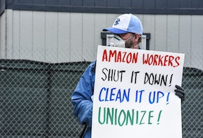 NEW YORK, NY - MAY 01: People protest working conditions outside of an Amazon warehouse fulfillment center on May 1, 2020 in the Staten Island borough of New York City. People attending the protest are concerned about Amazon's handling of the coronavirus and are demanding more safety precautions during the pandemic. (Photo by Stephanie Keith/Getty Images)